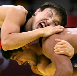 Kazakhstan's Leonid Spiridonov (top) grimaces as he wrestles India's Sushil Kumar (bottom) in the men's freestyle 66kg bronze medal wrestling match at the Aspire Hall for the 15th Asian Games in Doha, 14 December 2006.  South Korea's Baek Jin-Kuk defeated Japan's Takafumi Kojima for the gold, with India's Sushil Kumar and Mongolia's Batzorig Buyanjav taking bronze. AFP PHOTO/RABIH MOGHRABI