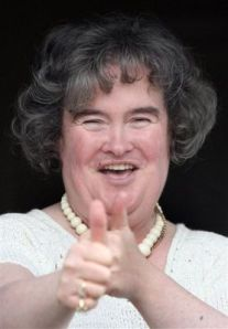 """Susan Boyle, who's performance on the television show """"Britain's Got Talent"""" wowed the judges, gives the thumbs up at her home in Blackburn, Scotland, Thursday April 16, 2009. The frumpy 47-year-old, who says she's never been kissed, has gained celebrity fans and millions of admirers - including a fair number of men - since appearing on the show. Her fame has been fueled by new technology, with a clip of her performance viewed more than 12 million times on YouTube.(AP Photo/Andrew Milligan-pa)"""